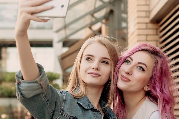 Przyjaciele robiący selfie smartfonem i robiący miny i zabawne. zbliżenie dziewcząt śmieszne miny i uśmiechając się do selfie. dwie szczęśliwe dziewczyny robiące zdjęcie smartfonem w mieście