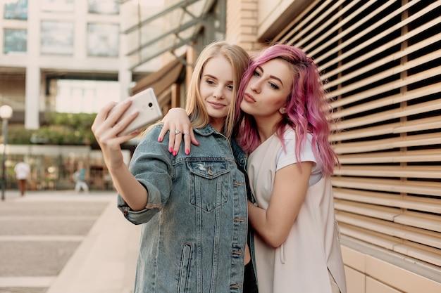 Przyjaciele robiący selfie smartfonem, robiący miny i zabawni. zbliżenie dziewcząt śmieszne miny i uśmiechając się do selfie. dwie szczęśliwe dziewczyny robiące zdjęcie smartfonem w mieście