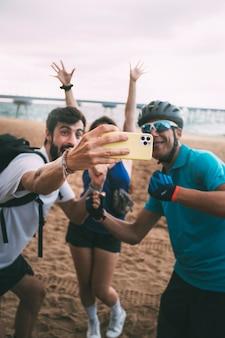 Przyjaciele robiący selfie telefonem na plaży skup się na dłoni i telefonie technologia przyjaźni