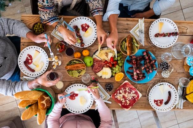 Przyjaciele rodziny bawią się razem zimą jedząc jedzenie na drewnianym stole