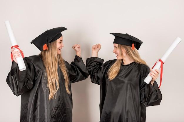 Przyjaciele są pogodni na ceremonii ukończenia szkoły