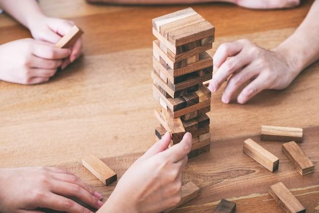Przyjaciele siedzą i grają razem w drewnianą grę tumble tower