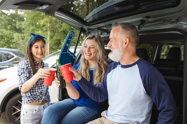 Przyjaciele siedzą i piją w bagażniku samochodu na imprezie na tylnej klapie
