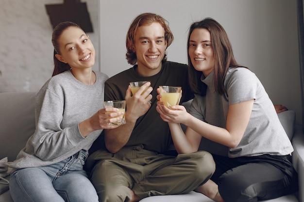 Przyjaciele siedzą na łóżku w pokoju z sokiem pomarańczowym