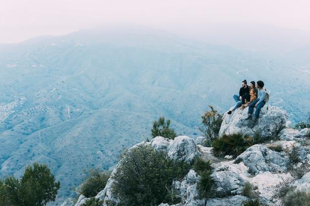 Przyjaciele siedzą na skale w przyrodzie