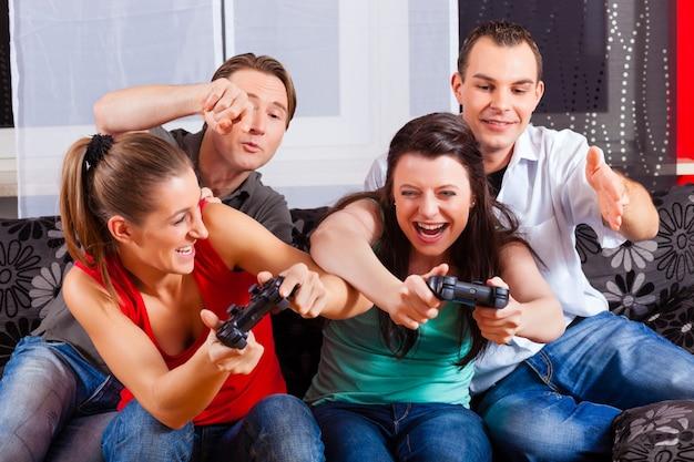 Przyjaciele siedzą przed pudełkiem konsoli do gier