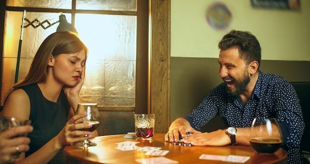 Przyjaciele siedzą przy drewnianym stole. przyjaciele bawią się podczas gry planszowej