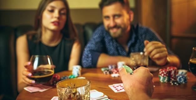 Przyjaciele siedzą przy drewnianym stole. przyjaciele bawią się podczas gry w gry planszowe.
