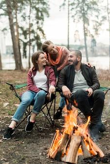 Przyjaciele siedzą przy ognisku