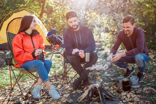 Przyjaciele siedzą przy ogniu i spędzają razem czas. młody człowiek po prawej trzyma grilla z kiełbaskami w ogniu. gotują i palą. inny facet na to patrzy. młoda kobieta uśmiech.