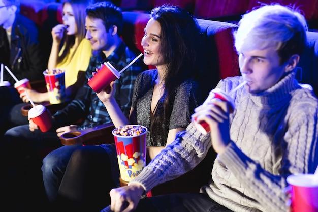 Przyjaciele siedzą razem i jedzą popcorn podczas oglądania filmów w kinie