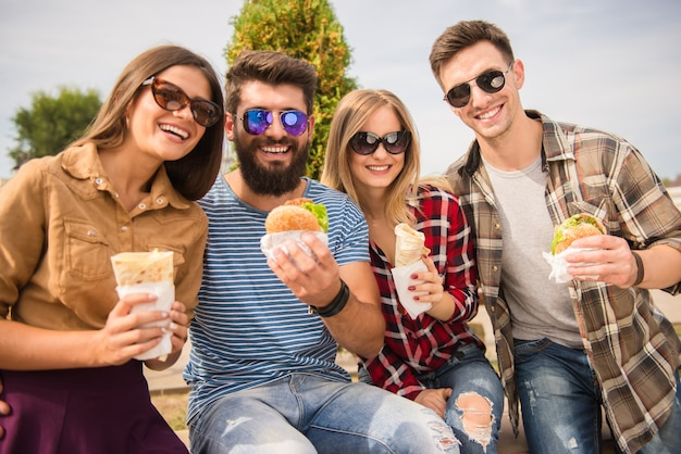 Przyjaciele siedzą w parku i jedzą fast foody.
