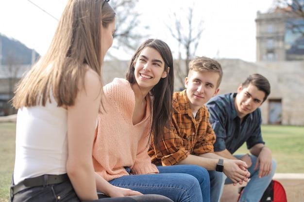 Przyjaciele siedzą w parku, rozmawiają i śmieją się