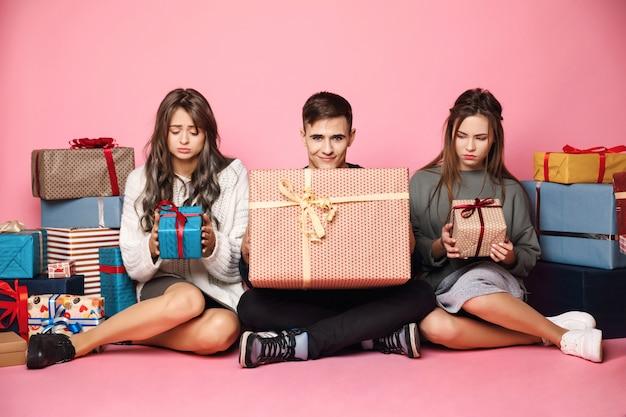 Przyjaciele siedzą wśród świątecznych prezentów. facet trzyma duże pudełko, womans mało.