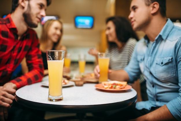 Przyjaciele siedząc przy stole w kręgielni, planszy. aktywny wypoczynek, zdrowy tryb życia, miska