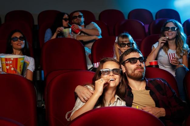 Przyjaciele siedząc w kinie, jedząc popcorn i wodę pitną