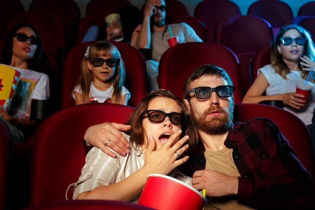 Przyjaciele siedząc w kinie oglądają film jedzący popcorn i wodę pitną.