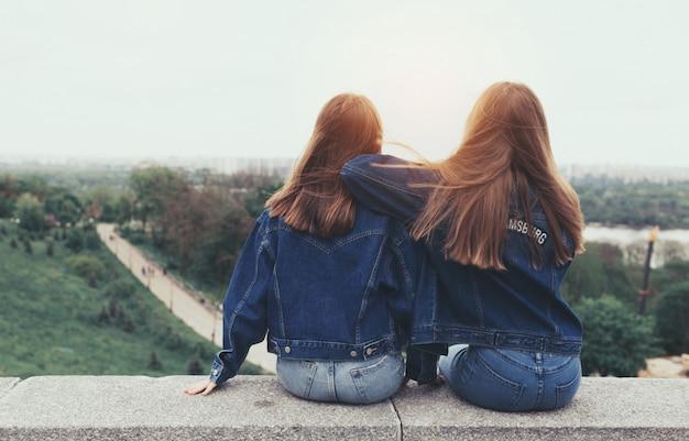 Przyjaciele siedząc w parku miejskim i podziwiając zachód słońca