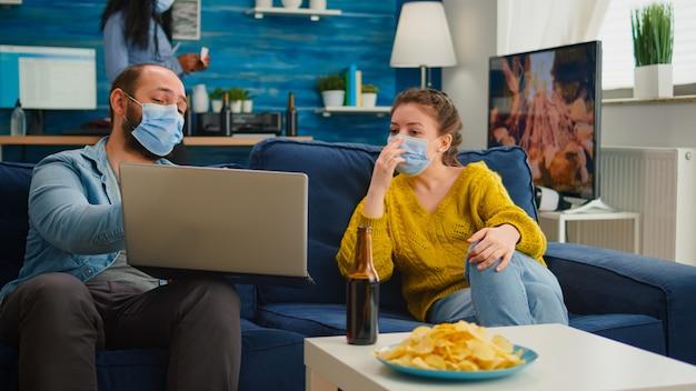 Przyjaciele siedzący na kanapie patrzący na laptopa towarzysko podczas imprezy noszący maskę ochronną utrzymujący dystans społeczny przed pandemią koronawirusa zapobiegają rozprzestrzenianiu się wirusa. osoby korzystające z wolnego czasu