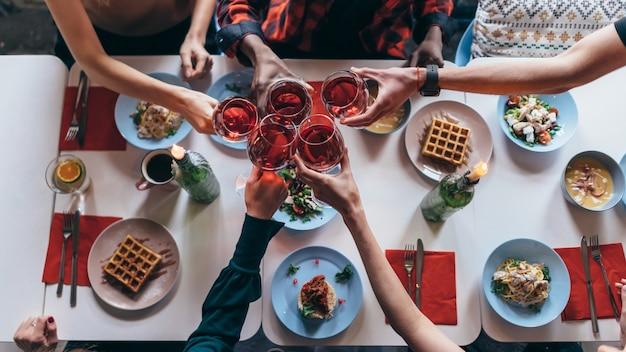 Przyjaciele siedzący przy stole, picie wina brzęk kieliszków.