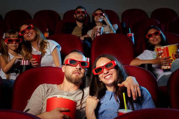 Przyjaciele siedzący w kinie oglądają film jedzący popcorn i wodę pitną.