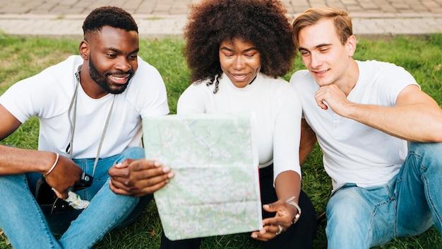 Przyjaciele siedzi na trawie i patrzeje mapę