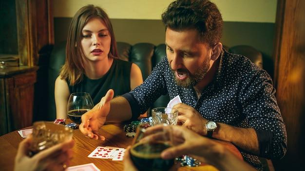 Przyjaciele siedzi przy drewnianym stole. przyjaciele zabawy podczas gry planszowej.