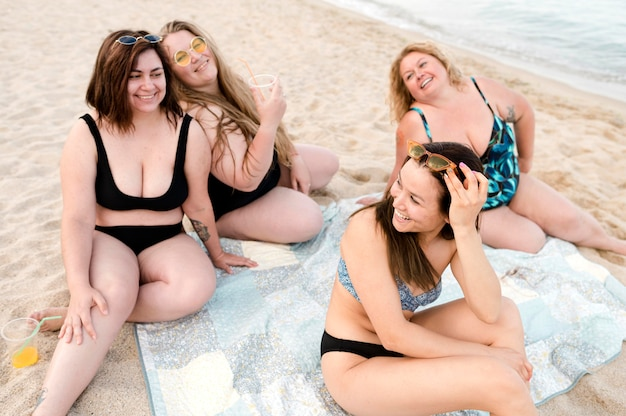 Przyjaciele siedzi przy plażowym wysokim widokiem