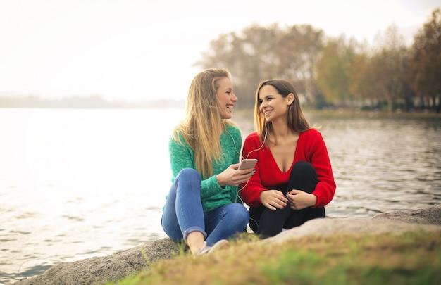 Przyjaciele słuchają muzyki przez słuchawki, siedzą wzdłuż brzegu rzeki
