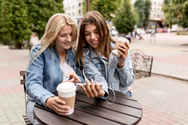 Przyjaciele słuchając muzyki trzymając kilka filiżanek kawy