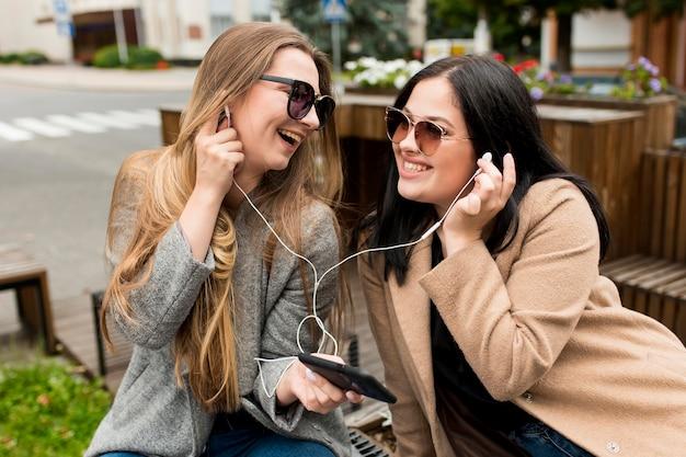 Przyjaciele słuchający muzyki przez słuchawki