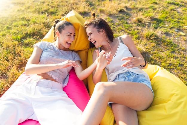 Przyjaciele śmieją się i siedzą na pufach