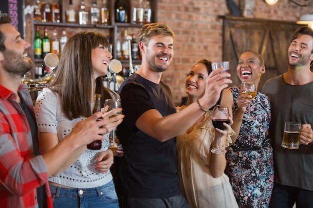 Przyjaciele śmieją się razem trzymając napoje