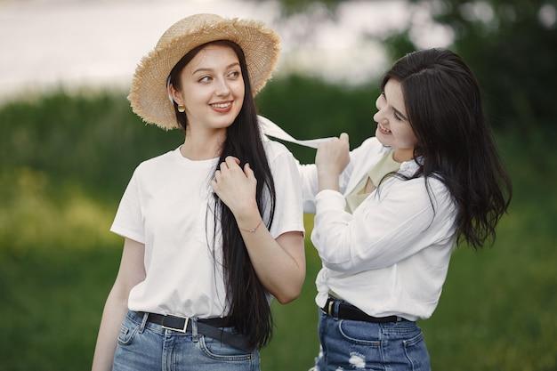 Przyjaciele spacerują. dziewczyna w kapeluszu. kobieta w białej koszulce.