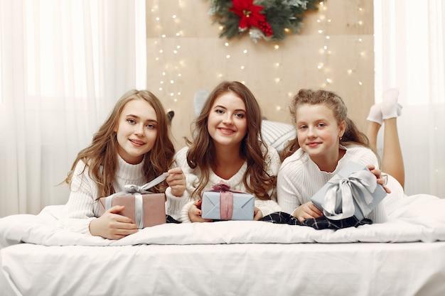 Przyjaciele spędzali czas w domu. dwie dziewczyny z prezentem na boże narodzenie. siostry razem.
