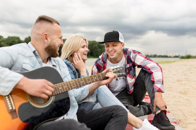 Przyjaciele śpiewają i grają na gitarze na plaży