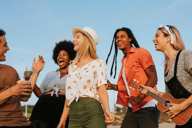 Przyjaciele śpiewają i tańczą na plaży