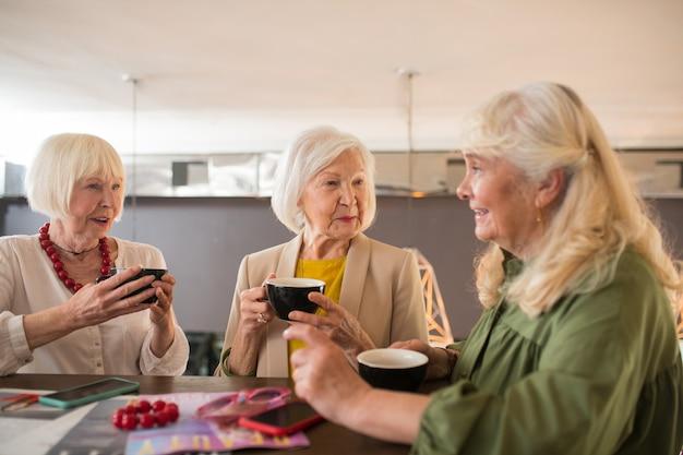 Przyjaciele. starzy przyjaciele spędzają razem czas i piją kawę w kawiarni?