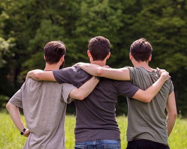 Przyjaciele stojący na polanie z rękami na ramionach