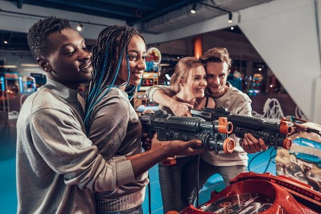 Przyjaciele strzelają do czarnych pistoletów w salonie gier.