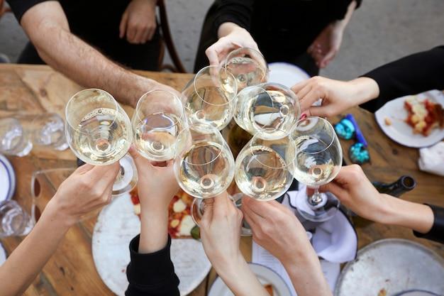 Przyjaciele stukają kieliszkami z białym winem podczas imprezy na świeżym powietrzu