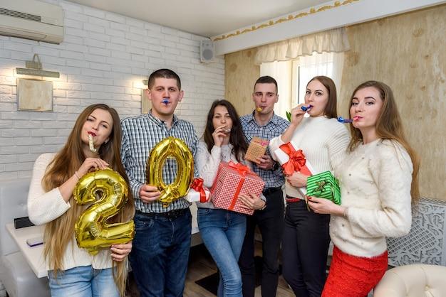 Przyjaciele świętują urodziny w kawiarni i pozują do kamery