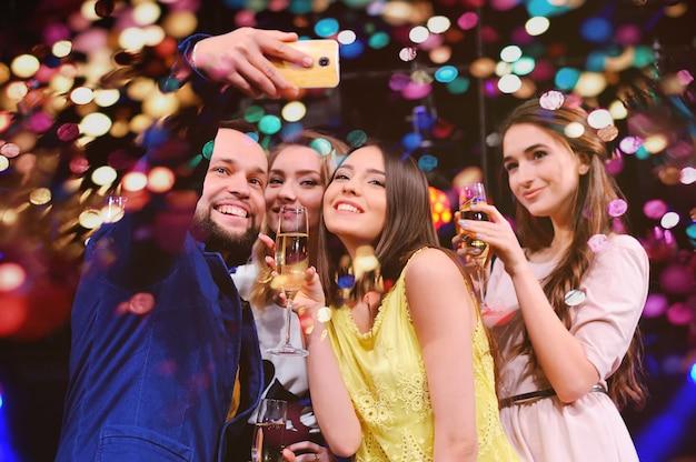 Przyjaciele świętują wydarzenie, śmiejąc się, tańcząc i pijąc szampana