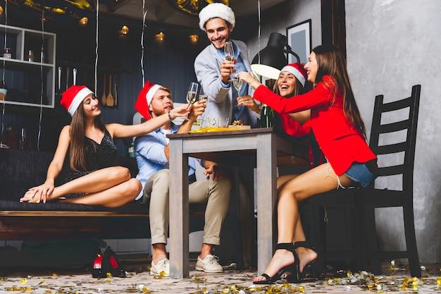 Przyjaciele świętujący boże narodzenie lub nowy rok. stolik z szampanem