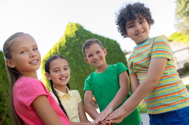Przyjaciele. szczęśliwi, wesoły uczniowie w jasnych ubraniach, trzymający się za ręce jako znak silnej przyjaźni stojącej w parku w pogodny dzień