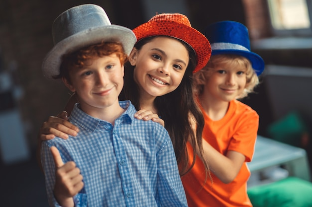 Przyjaciele. trzech przyjaciół w czapeczkach pozuje do zdjęcia