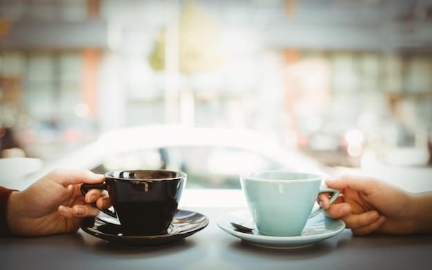 Przyjaciele trzyma filiżankę kawy