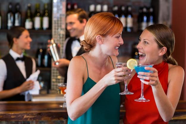Przyjaciele trzyma koktajl przed kontuarem baru