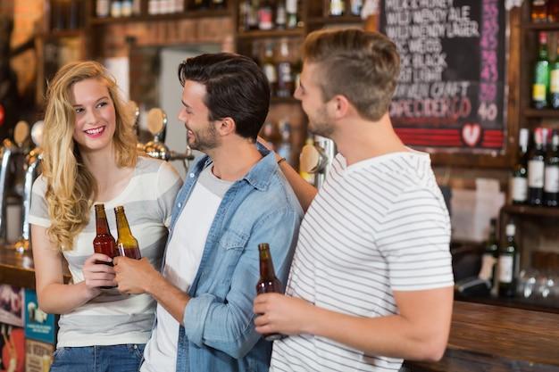 Przyjaciele trzyma piwne butelki przy pubem