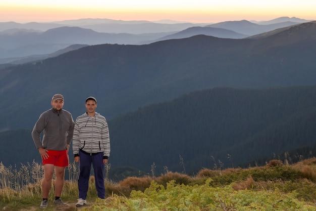 Przyjaciele turystów stojących na wzgórzach karpat z widokiem na zachód słońca na horyzoncie.